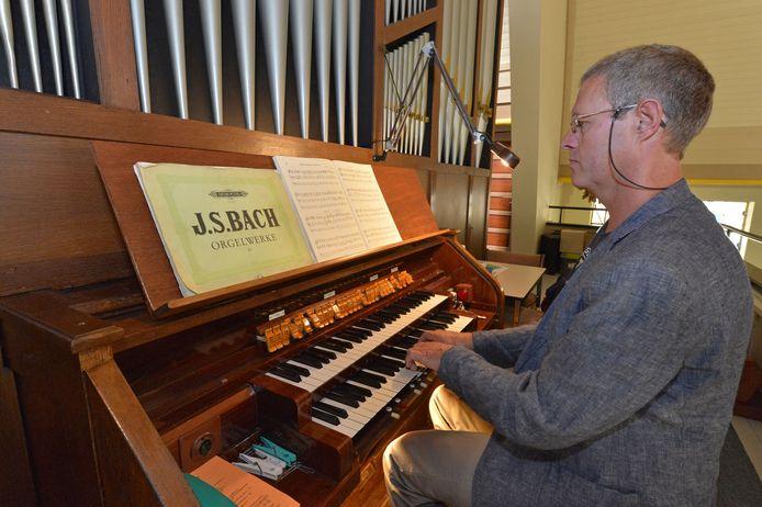 Jan van den Brand achter het orgel van de Julianakerk. Hij is coördinator van de orgeldag.
