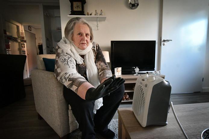 Gonnie Heupers bij het -niet aangesloten- kacheltje dat ze kreeg van de eigenaren van De Eik om toch een aangename temperatuur in haar appartement te krijgen.