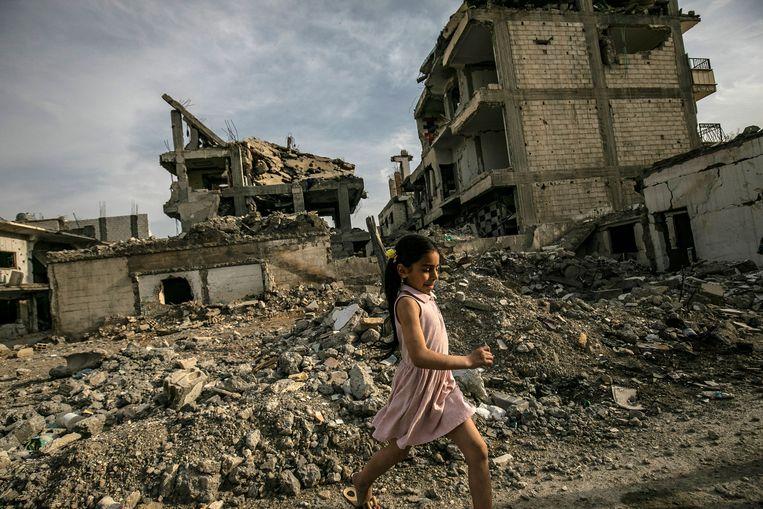 Een meisje loopt door het puin van de stad. De verwoesting nog steeds zo enorm dat je het benauwd krijgt door het stof van losliggend puin.  Beeld AFP