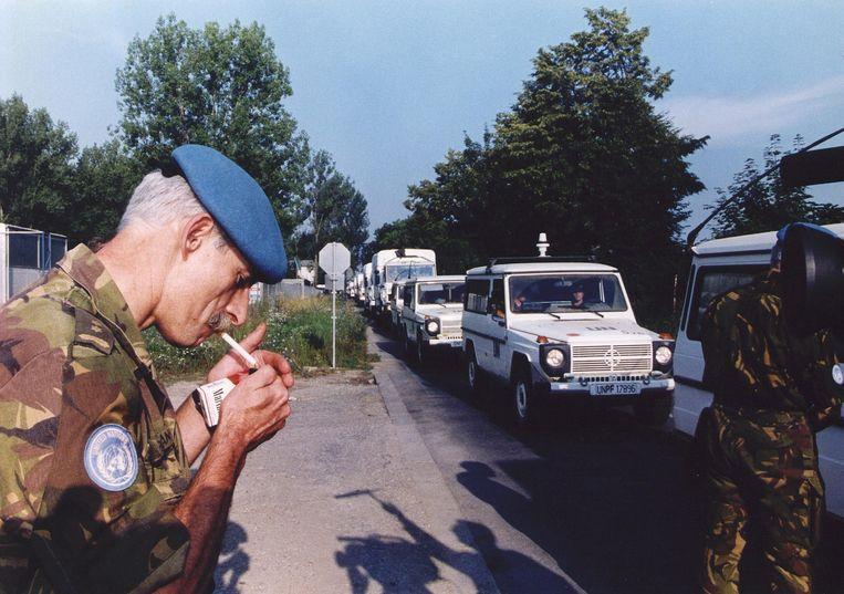 1995: Overste Karremans steekt een sigaret op, terwijl hij bij de poort van het VN-kamp in Zagreb de aankomst van Dutchbat gadeslaat. Beeld ANP