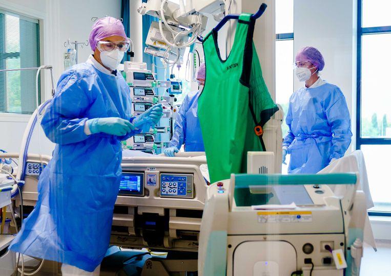 Medewerkers geven zorg aan een coronapatiënt op de intensive care. Beeld ANP