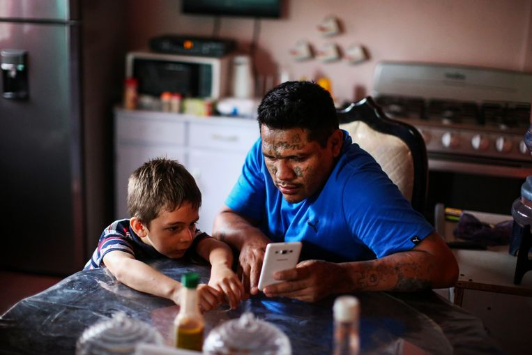 Raúl Valladares kijkt naar een filmpje met zijn stiefzoon Josue. Beeld JOSE CABEZAS