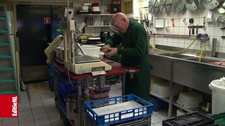 Een groenteboer snijdt een avocado open in een item van EditieNL. Beeld EditieNL/RTL