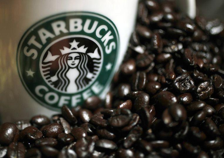 Starbucks-mok tussen de koffiebonen. Beeld reuters