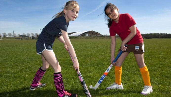 Twee hockeymeiden van Fletiomare, Kate Steunenberg (links, 8) en Valentina Toci (9), op het weiland bij sportpark Rijnvliet. De gemeente wil hier nieuwe hockeyvelden aanleggen.