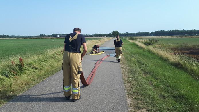 De slangen worden na het blussen van de brand in Vlijmen weer opgerold.