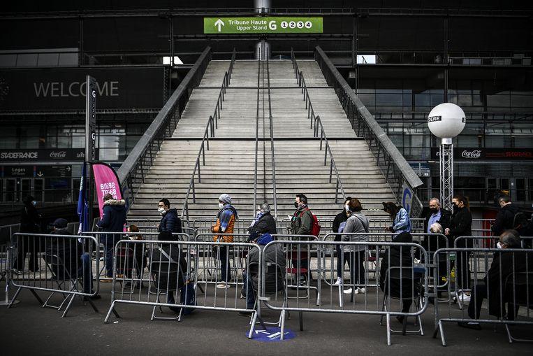 In de rij in het Stade de France, in afwachting van een coronavaccinatie.  Beeld Christophe Archambault / AFP