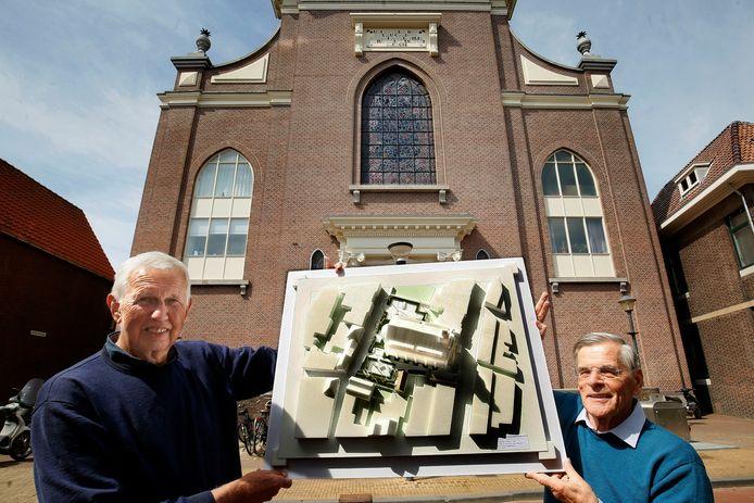 Stichtingsvoorzitter Ewald Klaui en stedenbouwkundige Bert Welmers (links) met de maquette  waarop naast de kerk een nieuwe woning staat daarachter een pleintje waar de vier glas-in-loodramen komen te staan.