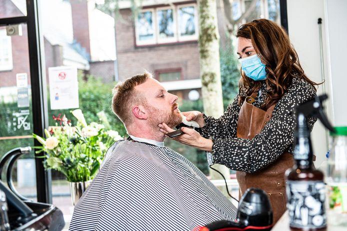Kapster en barbier Fleur van Dijk heeft haar stoel op de eerste dag dat ze open mag direct goed gevuld. Maarten Marchand is blij dat hij van zijn coronakapsel wordt verlost.