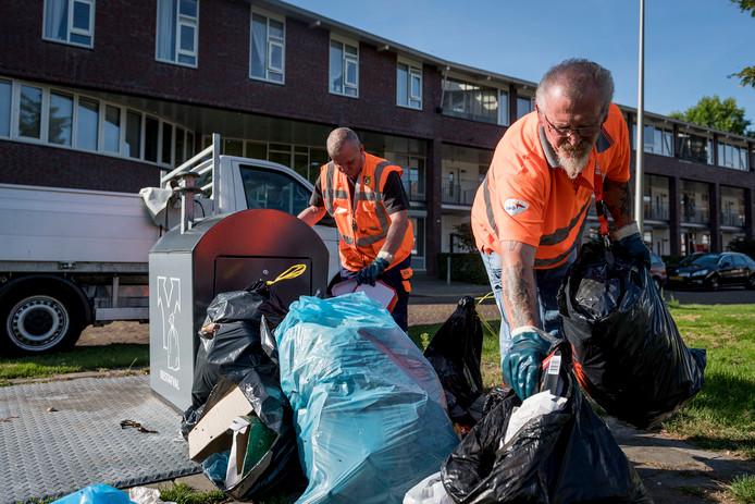 Medewerkers van Gildebor halen het afval weg dat Hengeloërs naast de container hebben geplaatst.