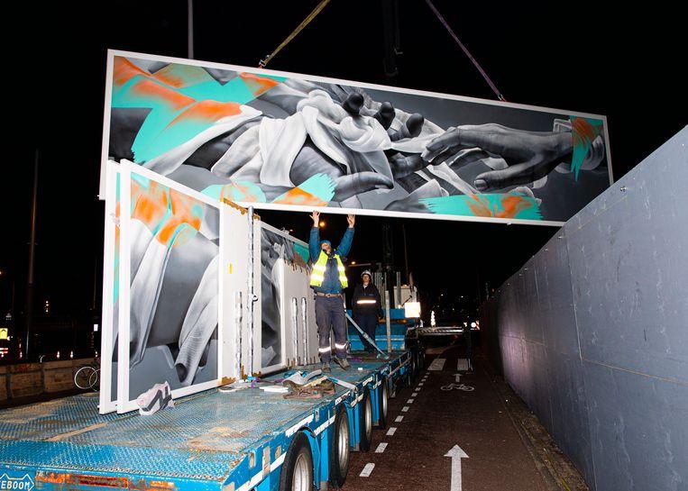 De mural 'Closer in Distance' wordt geplaatst aan de De Ruijterkade. Beeld Lin Woldendorp