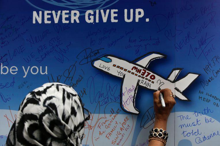Een vrouw schrijft een boodschap voor de passagiers van de vermiste vlucht MH370 op een banner ter gelegenheid van een herdenkingsceremonie in Maleisië. Beeld EPA