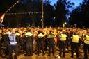 De politie stuurt aan op het vertrek van de menigte.