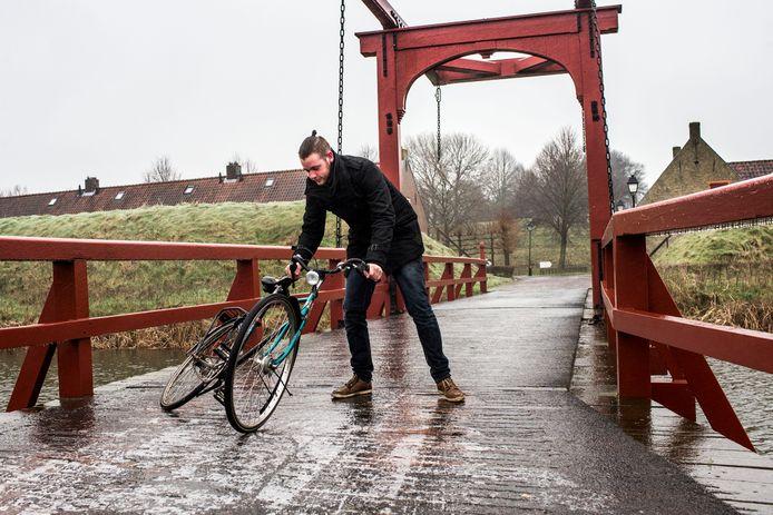 Een fietser loopt met zijn fiets aan de hand over een brug in het vestingdorp Bourtange. Het KNMI waarschuwde verkeersdeelnemers in het noordoosten van het land voor gladde wegen en een verhoogde kans op ongelukken.