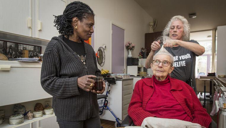 Mevrouw Kisman (88) krijgt hulp van thuiszorgster Elly de Weij (rechtsachter) en Lucille Vyent (l). De Weij krijgt al sinds januari geen salaris meer. Beeld Dingena Mol