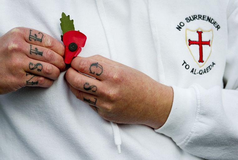 Een lid van de English Defence League spelt zaterdag een embleem op. Foto © Koen van Weel/anp<br /> Beeld
