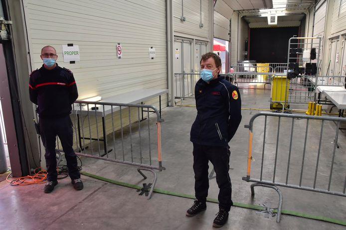 Pieter Altes (links) en Bruno Lemant, lid van het team Interventie Gevaarlijke Stoffen (IGS), bij de uitgang van de ontsmettingszone op de terreinen van Kortrijk Xpo.