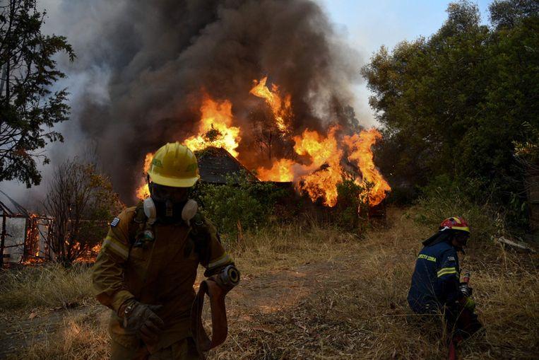 Brandweermannen aan het werk in de buurt van de Griekse stad Patras, waar vier dorpen geëvacueerd werden. Beeld AFP