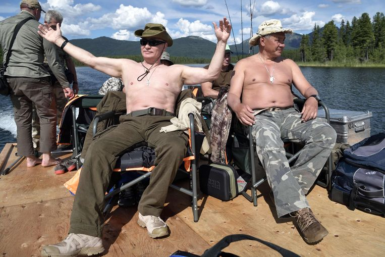TOPSHOT - Russian President Vladimir Putin (L), accompanied by defence minister Sergei Shoigu, gestures as he fishes in the remote Tuva region in southern Siberia. The picture taken between August 1 and 3, 2017. / AFP PHOTO / SPUTNIK / Alexey NIKOLSKY Beeld AFP