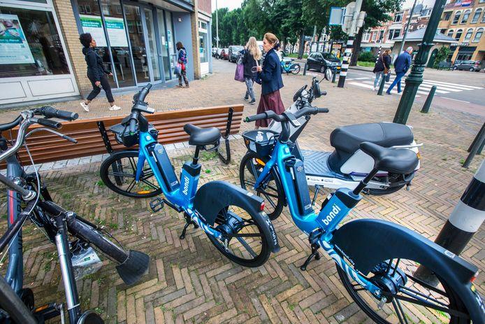 Huurfietsen op de stoep. De blauwe leenfietsen van Bondi staan op de Haagse Frederik Hendriklaan.