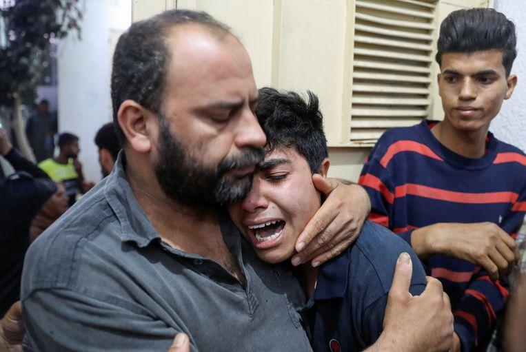 Familieleden van een Palestijns slachtoffer troosten elkaar in een ziekenhuis in Gaza.  Beeld REUTERS