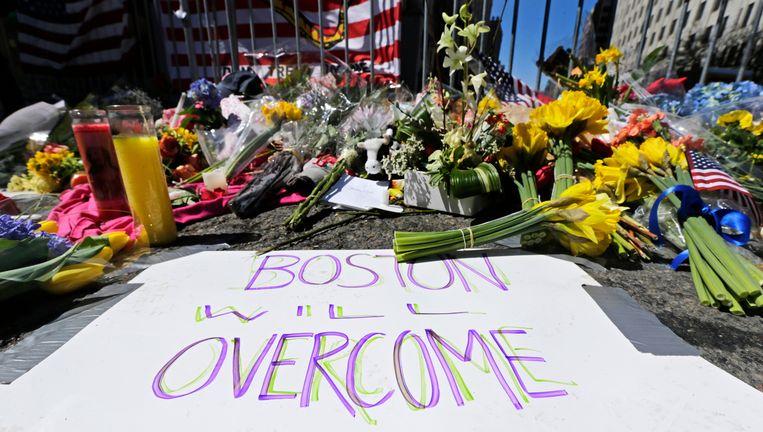 Mensen hebben bloemen neergelegd op de plaats waar de bommen ontploften. Op het papier staat de tekst 'Boston zal overwinnen'. Beeld AP