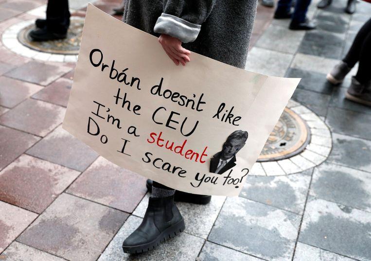 'Orbán houdt niet van de CEU (de Central European University, red.). Ik ben student. Boezem ik u ook angst in?' staat te lezen op een meegevoerd protestbord in 2018. De universiteit, in 1991 gesticht door de van oorsprong Hongaarse investeerder en filantroop George Soros, moest Hongarije twee jaar geleden na een wetswijziging verlaten. Beeld REUTERS