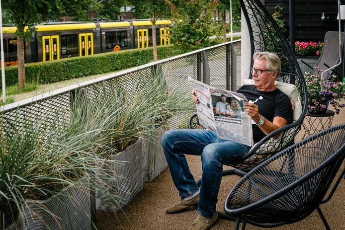 Ton Standaar op zijn balkon aan de Praagsingel met de lawaaiige tram op de achtergrond.