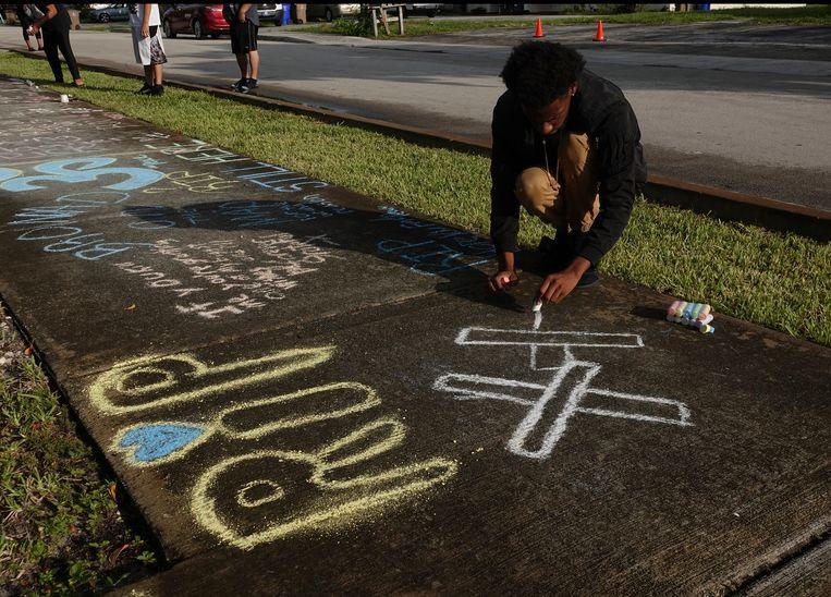 Een jonge fan van de vorig jaar vermoorde rapper XXXTentacion schrijft een boodschap op de stoep bij zijn huis. Archiefbeeld. KJ Balla is de derde rapper in vier maanden die in Brooklyn is doodgeschoten.