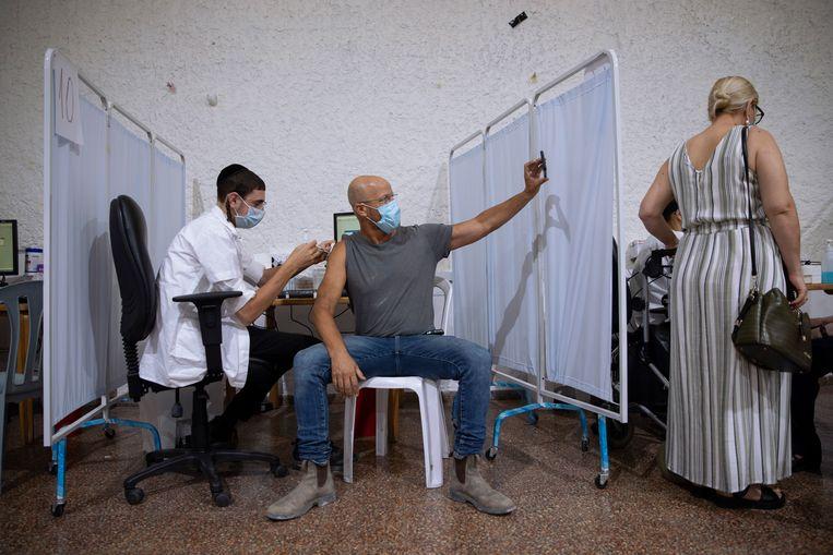 Een Israeliër krijgt een derde Pfizerprik. Het land maakte deze week bekend een derde prik beschikbaar te willen stellen voor iedereen van 12 jaar en ouder.  Beeld AP