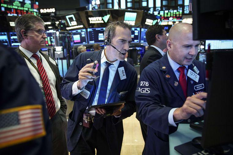 Bankiers volgen de ontwikkelingen van de Dow Jones in New York. Beeld AFP