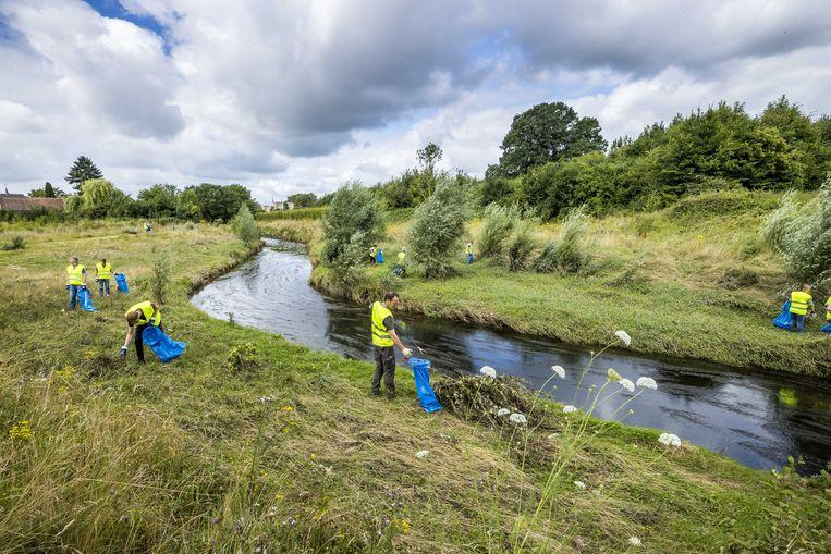 Vrijwilligers ruimen maandag troep op bij het buurtschap Abshoven, langs de Geleenbeek. Beeld ANP