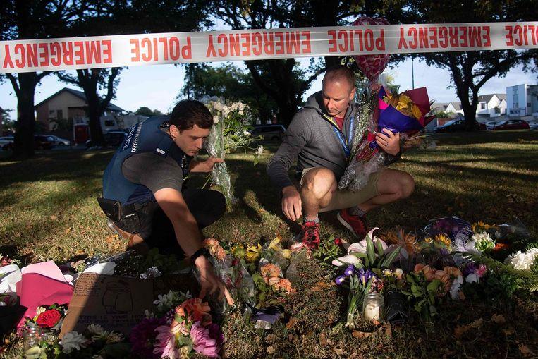 Een agent verzamelt bloemen bij een politiecordon aan een moskee in Christchurch. Beeld AFP