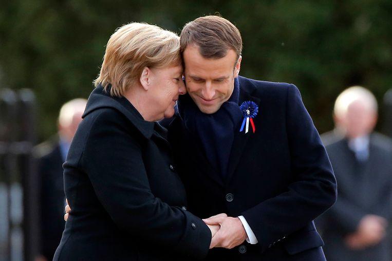 De Duitse bondskanselier Angela Merkel en de Franse president Emmanuel Macron houden elkaars handen vast tijdens de ceremonie in Compiègne. Daar werd op 11 november 1918, in een treinwagon, de Duitse capitulatie bezegeld en een einde gemaakt aan WOI. Beeld AP