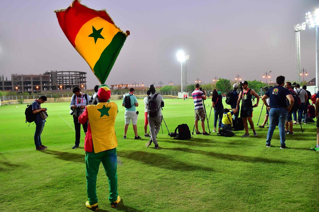Een fan zwaait op de laatste training van zijn land met een Senegalese vlag.