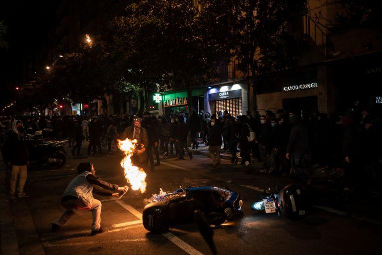 Een betoger steekt een motorfiets van de politie in brand tijdens het protest tegen de opsluiting van een Catalaanse rapper.  Beeld AP