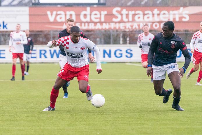 Tyrone Conraad (links) versnelt namens Kozakken Boys langs de verdediger van Jong Sparta.