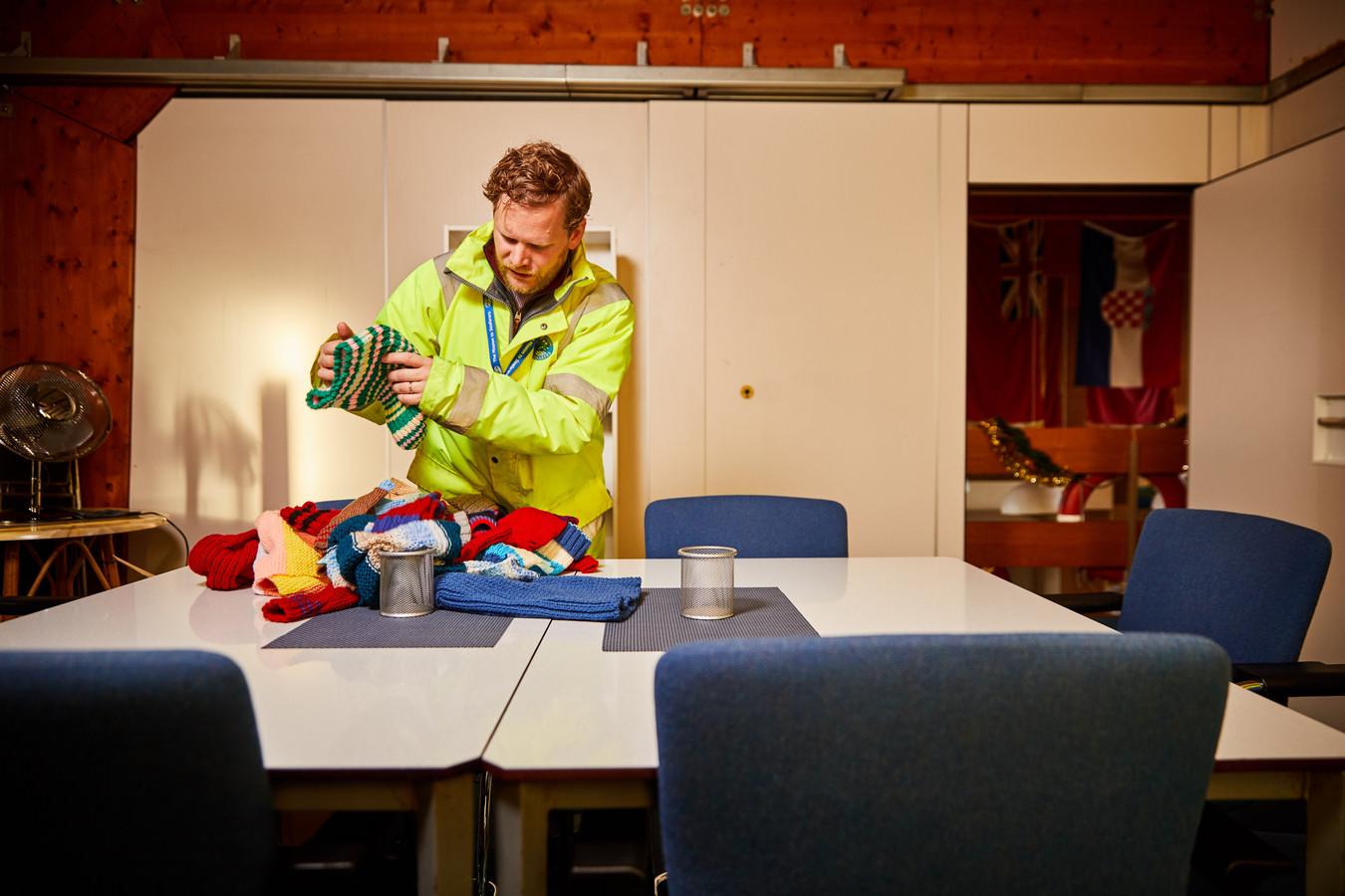 Dominee Dennis Woodward pakt in het Zeemanshuis in Schiedam mutsen in die hij aan boord van schepen uitdeelt.