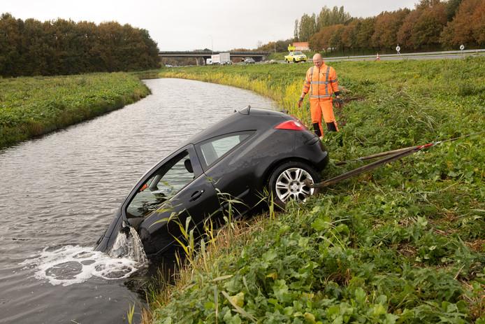 Bergers halen de auto uit het water.