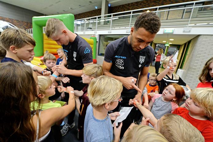 De Heracles spelers Cyriel Dessers en Mats Knoester delen handtekeningen uit aan hun jeugdige fans.