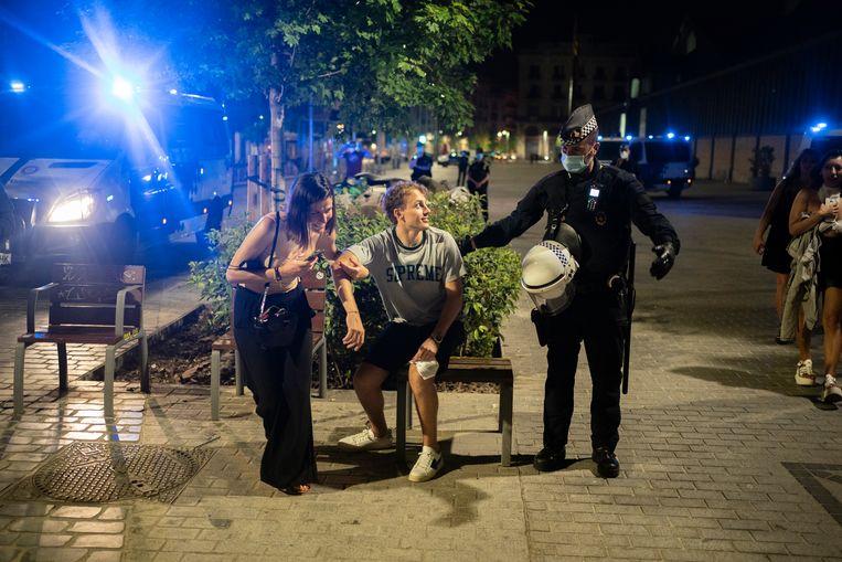 Een aantal jongeren in Barcelona worden door de politie weggejaagd.  Beeld AP