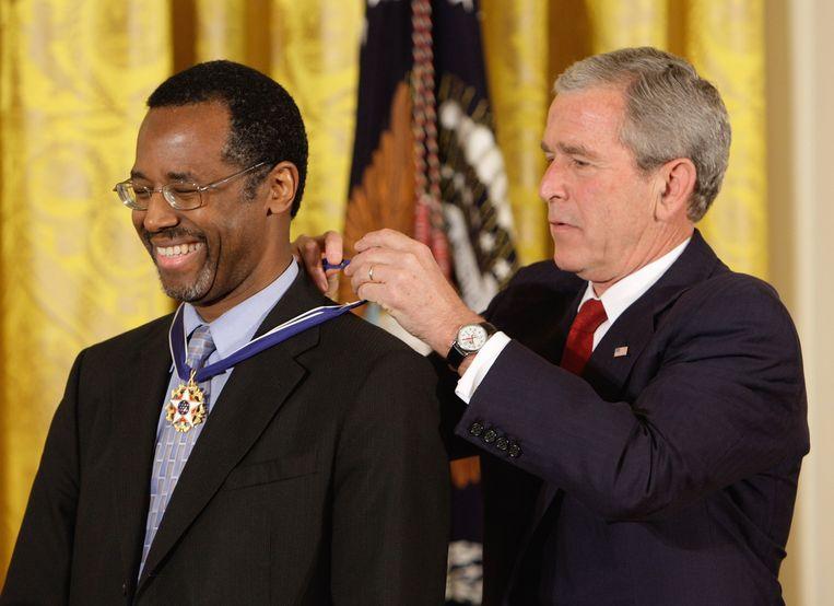 Ben Carson kreeg in 2008 de Presidental Medal of Freedom van toenmalig president George W. Bush. Het is een van de vele bekroningen in zijn leven. Beeld AP