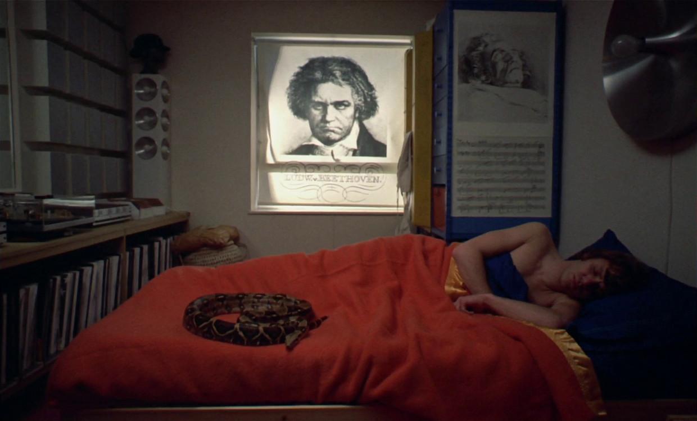 Still uit A Clockwork Orange (1971). Hoofdpersonage Alexander DeLarge slaapt met zijn idool Beethoven aan de muur.  Beeld