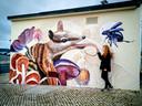 De Rotterdamse Nina Valkhoff bij de - in haar ogen bescheiden - muurschildering (21 m2) in Lissabon. ,,Iemand vroeg wat het voor een rat was. Maar het is helemaal geen rat, het is een numbat. Een Australische buidelmiereneter die sterk bedreigd wordt in zijn voortbestaan.''
