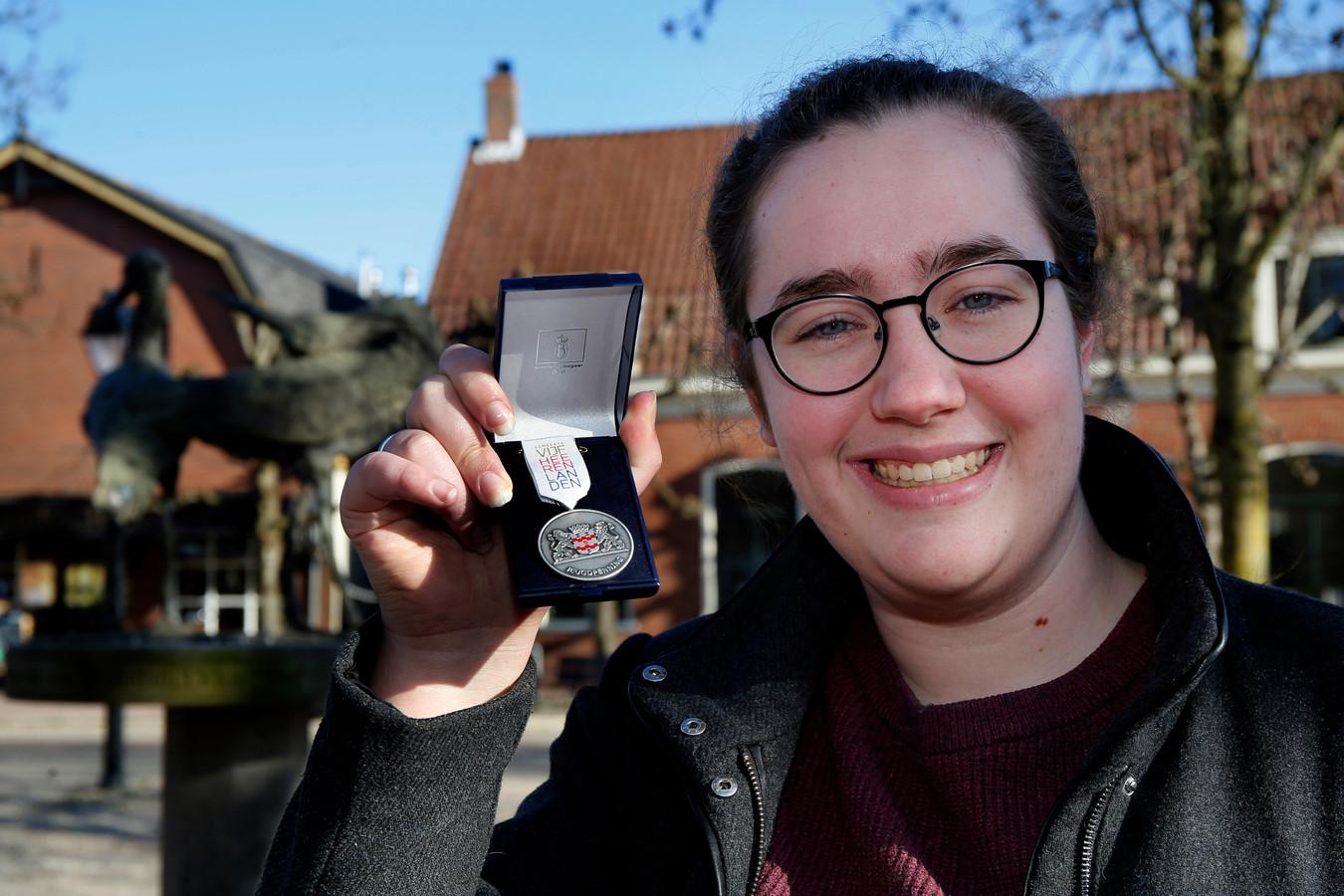 Emma van der Poel laat de penning zien die ze van de burgemeester kreeg uitgereikt.