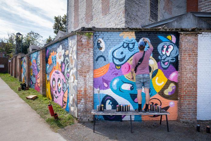 BORNEM Kunstenaar Bué The Warrior brengt street art aan op de kerkmuur aan de ingang van OLVP