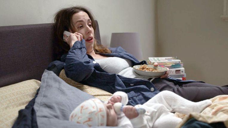 Scene uit de Netflix-serie The Letdown waarin hoofdpersoon Audrey met haar mobiel in de weer is terwijl de baby naast haar op bed ligt. Beeld Netflix