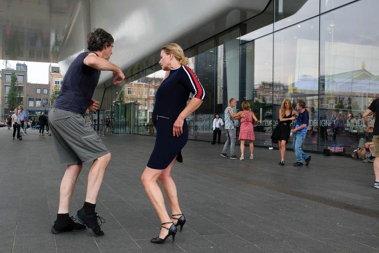 Mensen dansen onder de luifel van het Stedelijk Museum. Beeld Hollandse Hoogte / Ingrid de Groot