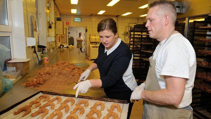 Rachel van Kommer en bakker Jan Koot keuren de gedraaide haantjes.