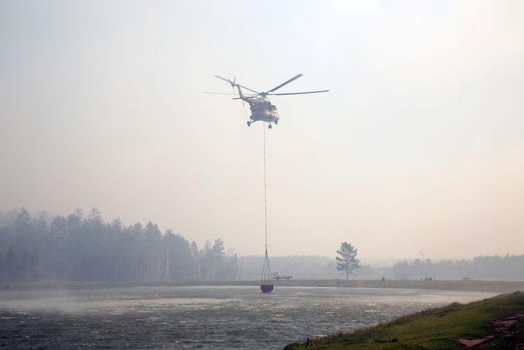 Een helikopter haalt water uit een meer om te blussen in Jakoetsk.  Beeld via REUTERS